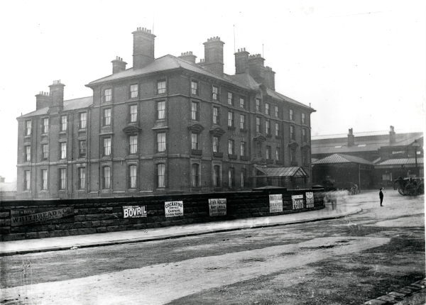 Exterior view of the MSLR's Royal Victoria Hotel in Sheffield. The photograph, dated around 1894, was taken near the end of Victoria Station Road. The low wall in the foreground displaying adverting posters is the boundary for the Smithfield Market. Shown in the station forecourt are two horse drawn carriages while a lone, unidentified, man stands in front of the hotel.