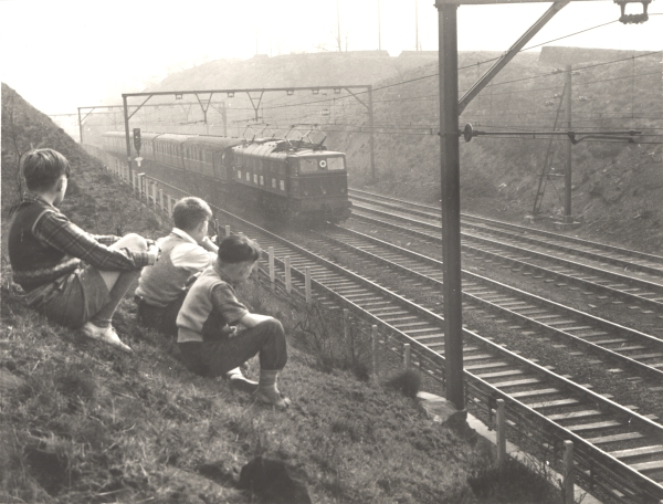 One of the EM2 Co-Co electric locomotives heads towards Oughty Bridge (now Oughtibridge) circa 1954. A small huddle of boys wearing the classic 'tank-top' sleeveless jumpers of the 1950's, watch the train approaching. How many of them grew up to be engine drivers, one wonders?