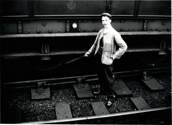 A portrait of a wheel-tapper at work, checking the wheels of a bogie carriage at Leicester Central station, circa 1910. The job of a wheel-tapper was to test wheels for cracks or fractures using a special wheel-tappers hammer (seen in the photograph),