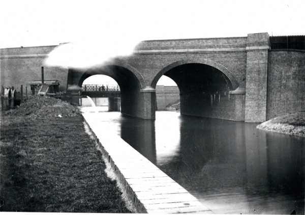 Bridge 378 carrying Upperton Road in Leicester looking west. The two-arch skew bridge looks to be complete, but there is a pumping engine spilling water into the rive on the left.