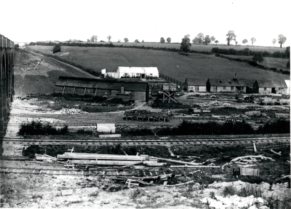 Walter Scott & Co.'s Helmdon yard, in the shadow of the new viaduct circa 1897. A network of railway tracks spread across the site and a coaling stage is visible in the centre of the picture. Next to the long shed is the water tower for the locomotives.
