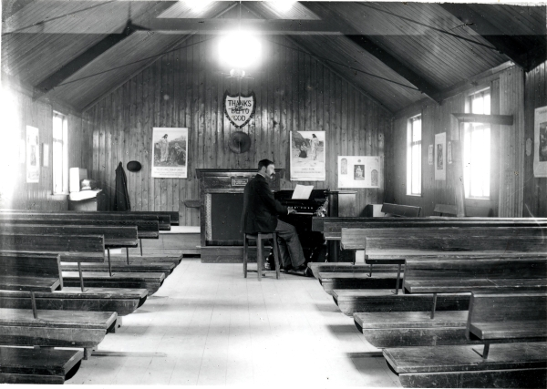 A view along the aisle towards an organist practising in the Navvy Mission room at Loughborough. Images depicting the life of Jesus Christ adorn the walls, and the Mission's motto, 'Thanks Be To God' is painted on a wooden shield above the pulpit. These humble surroundings helped to promote the simple, uncompromising message with which the Society hoped to reach their flock.