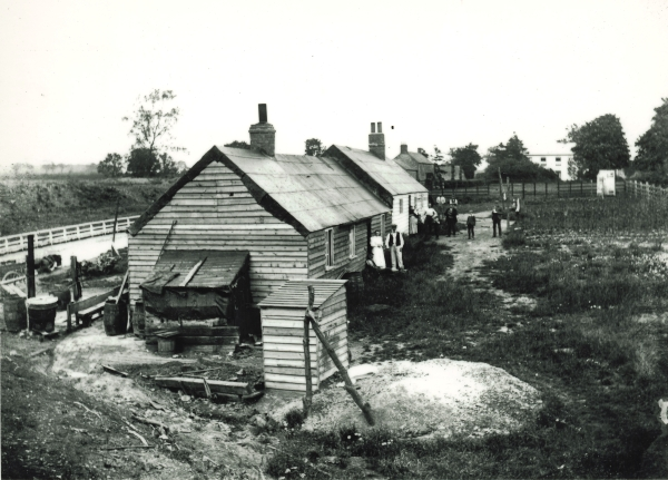 By the end of the nineteenth century the navvies' employers were far more willing to provide their workers with suitable accommodation. Photographed around 1897, these purpose built, temporary wooden huts formed part of the Barley Fields navvy settlement in Oxfordshire. On the right are the garden allotments in which the navvies could grow their own food.