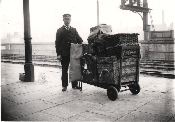 Porter Frank Freeman standing with a laden trolley on the platform of Leicester Central station, circa 1900.