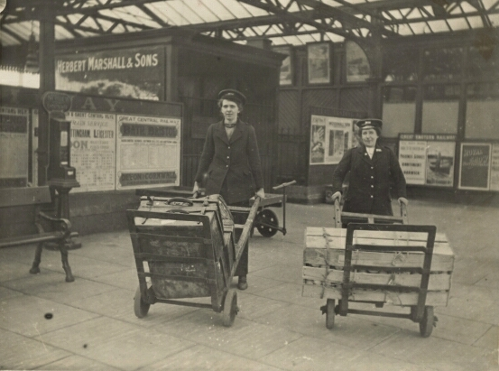 Two women porters at work on the platform of Leicester Central Station, circa 1918. The identity of the lady on the left is unknown, but the lady on the right of the photograph has been identified as being Lucy Lount.
