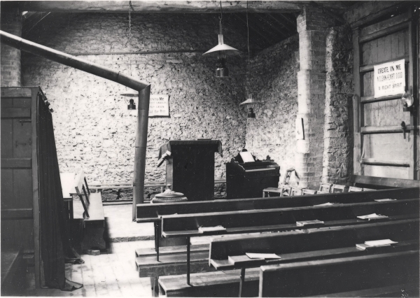 Inside a navvy mission room at Staverton, Northamptonshire. Located within a disused outbuilding, these premises would have served those navvies at work on Contract No.4 (Rugby to Woodford). Note the biblical texts placed on the walls, and the simple pulpit from which the 'message' was preached.