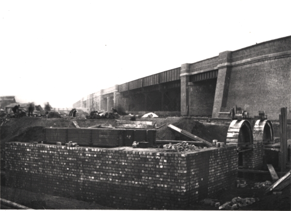 Upperton Road bridge crossed the London Extension and its sidings at Leicester Goods Yard. The main line itself passed beneath the double girder span visible to the left of the central iron section. Under construction in the foreground is the wagon repair shop, one of the few Great Central buildings that still stands today.