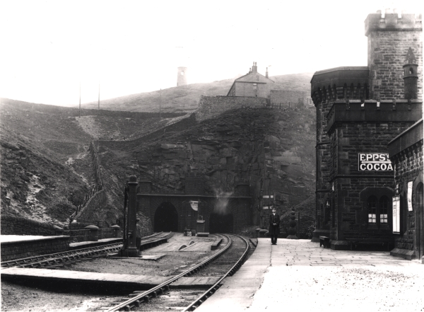 This rather atmospheric and picturesque location is the Great Central Railway's station at Woodhead in Cheshire. A proud railwayman stands impassively on the platform, as the west portals of the Woodhead Tunnel disappear into the Pennine rock beyond.
