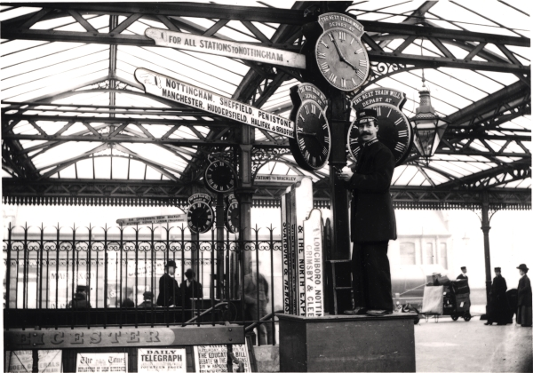 A Ticket Examiner, believed to be H. G. Banyard, adjusts the train time indicator on the platform of Leicester Central station in October 1902. Note the selection of destination finger boards emerging vertically from the pedestal.
