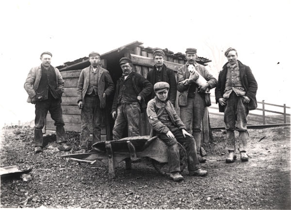A group of navvies pose for Newton's camera beside their hut in Leicester. Notice that despite their differing ages, these men are all wearing the unmistakable navvy dress of thick trousers, waistcoat, hat and neckerchief.