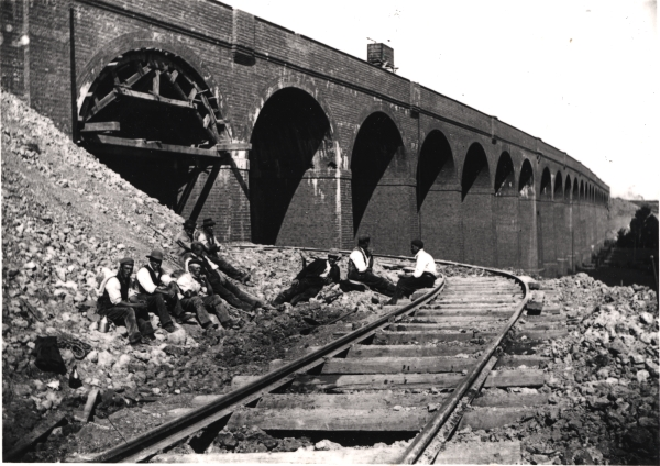 Photographed around 1897, a gang of navvies enjoy their lunch break beside the almost completed viaduct at Brackley. Ale was regularly consumed on such occasions, but as 'safe' drinking water was often hard to come by, low alcohol beer provided the navvy with one of the few viable alternatives with which to quench their thirsts.