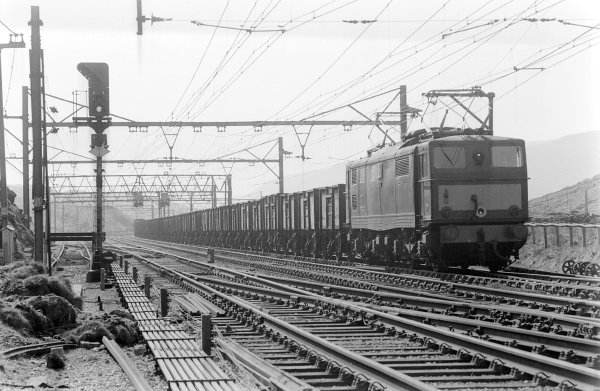 The completion of the Woodhead Route electrification in 1954 saw steam services gradually give way to the new electric locomotives. Here we see one of the EM1 type Bo-Bo electrics hauling a mineral train on the approaches to Woodhead Tunnel. Services such as these would have previously been handled by the successful O4 (8K) class locomotives before handing them over to the EM1's.