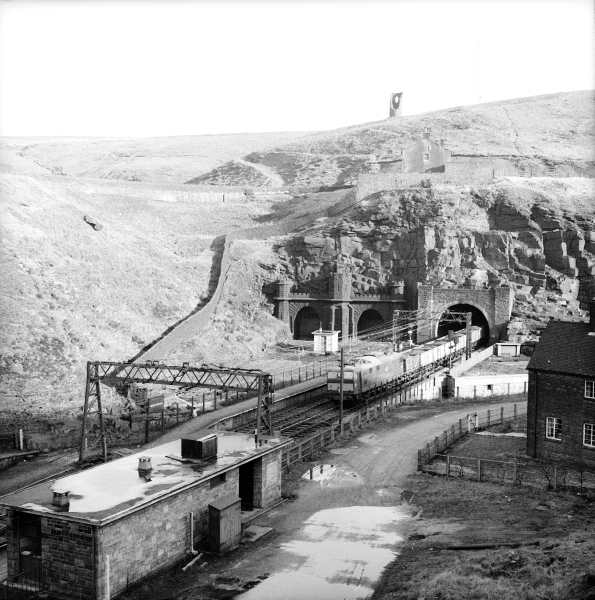 One of the EM1 electric locomotives emerges into Woodhead station from the new Woodhead Tunnel in February 1964. The old tunnels are to the left of the picture, while the station buildings have been demolished. Compare this with image L2376.
