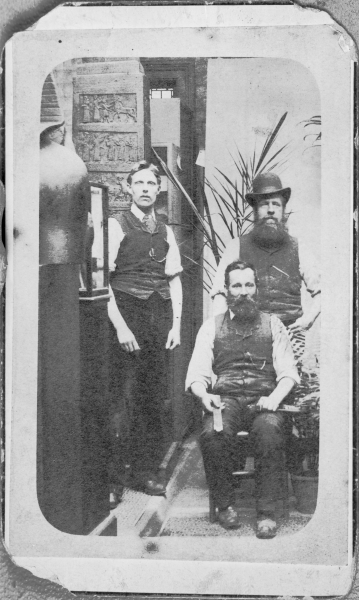The young man on the left of this photograph is S. W. A. Newton, pictured circa 1900 when he was 25. His father's business, Alfred Newton & Son, was the official photographer to Leicester Museums and many museum artefacts can be seen in the image. The identity of the other two gentlemen is unknown, although it is believed that the man sitting down is Alfred Newton himself.