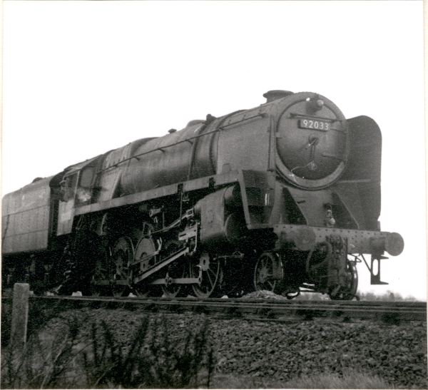 This photograph shows single chimney fitted class 9F 2-10-0, No. 92033, as it waits for a service train to pass at Whetstone.